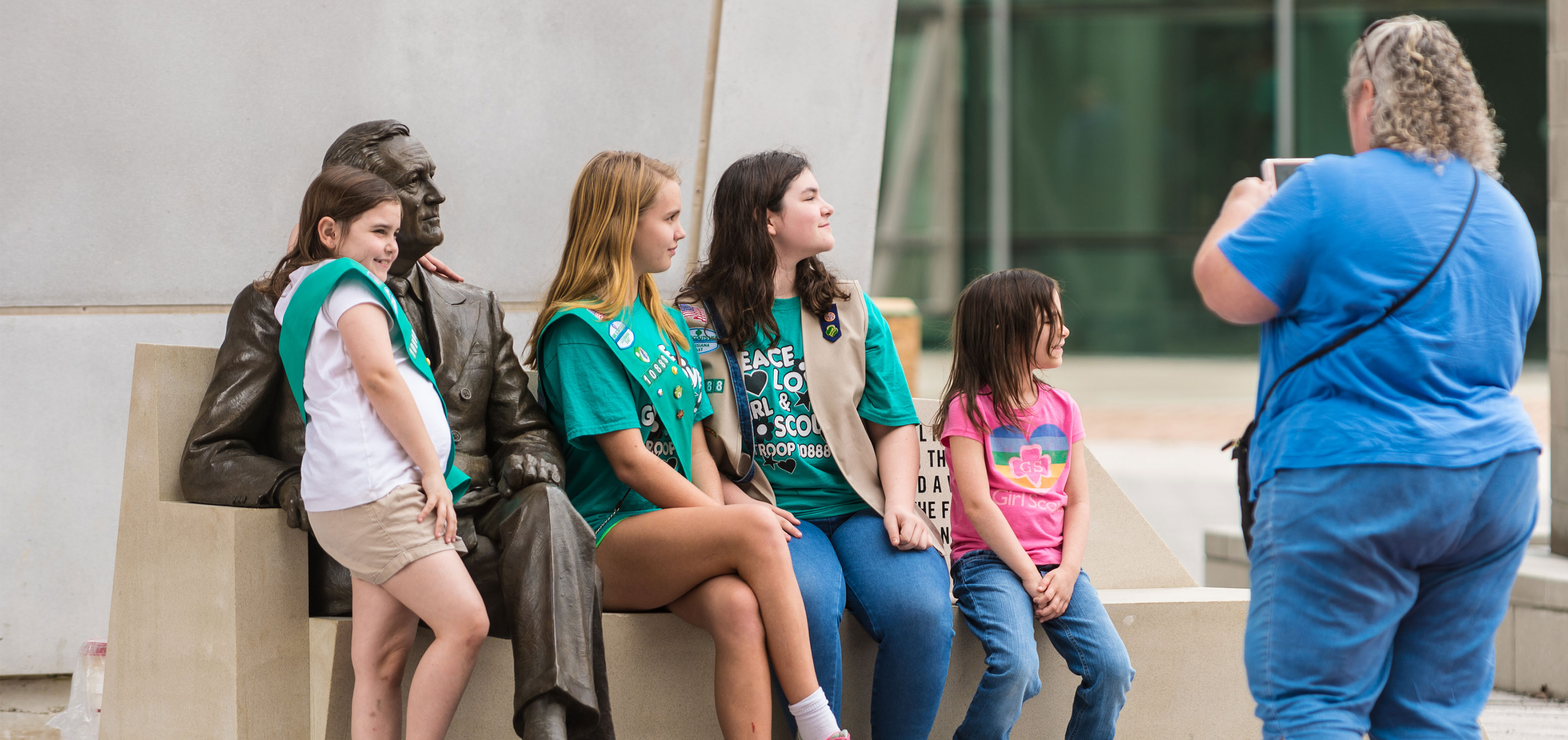 Kids and family posing with FDR statue at The National WWII Museum