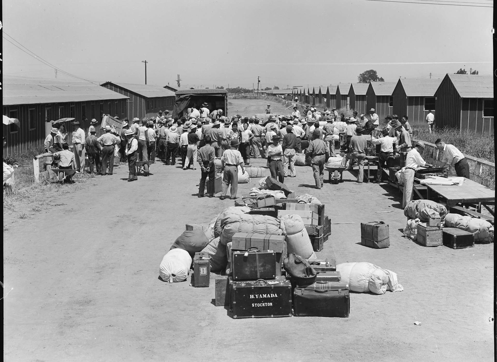 Japanese Americans arriving at an assembly center near Stockton, California. Their possessions are piled outside awaiting inspection before being transferred to the barracks (1942).