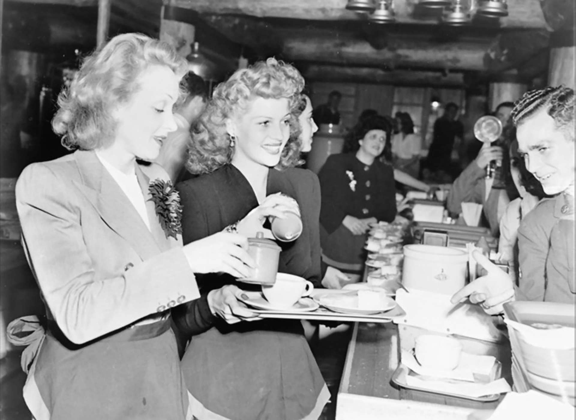 Actresses Marlene Dietrich and Rita Hayworth serve food to soldiers at the Hollywood Canteen in Hollywood, California.