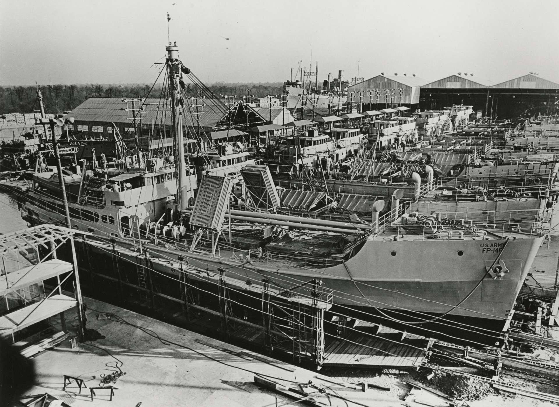One hundred FP, later designated FS (Freight, Supply) ships, were built at Industrial Canal on a moving assembly line. As each ship reached the end of the line it was launched, stern first, into the Industrial Canal for final testing. In this image, FP-146 is nearing completion and launch.