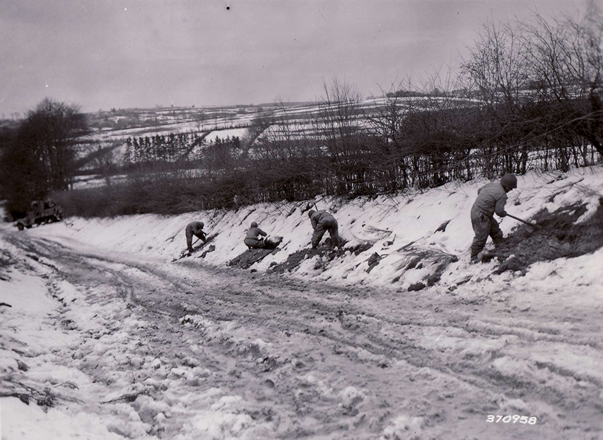 2nd Infantry Division soldiers dig in on a road bank and prepare defensive positions on the end of the Elsenborn Ridge on December 20, 1944. The National WWII Museum Digital Collections.