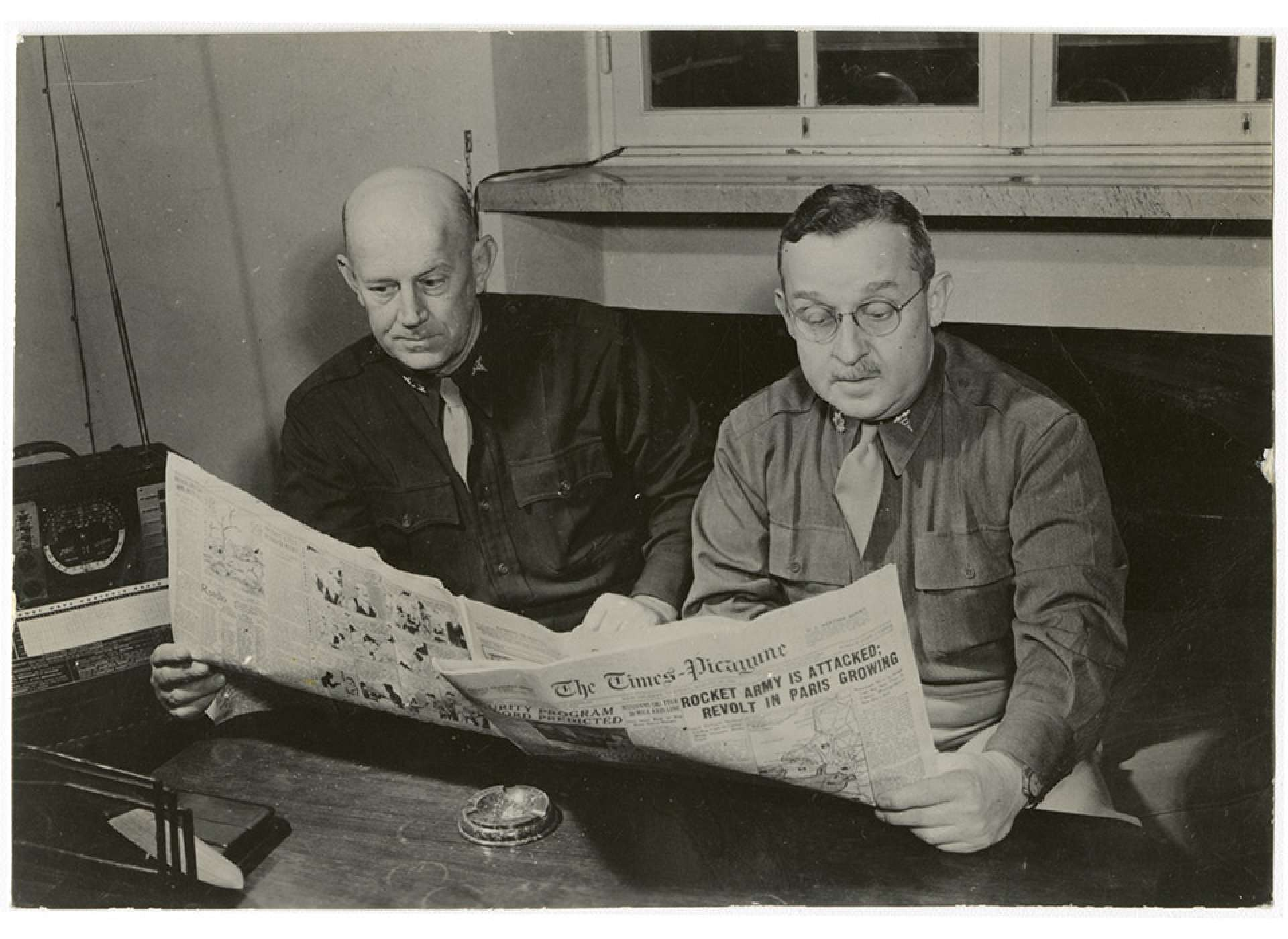 Home was never too far away. Colonel Royals and Major George Grant (L-R), the Commanding and Executive Officers of the 24th General Hospital, read copies of the New Orleans newspaper Times-Picayune in Florence. The National WWII Museum.