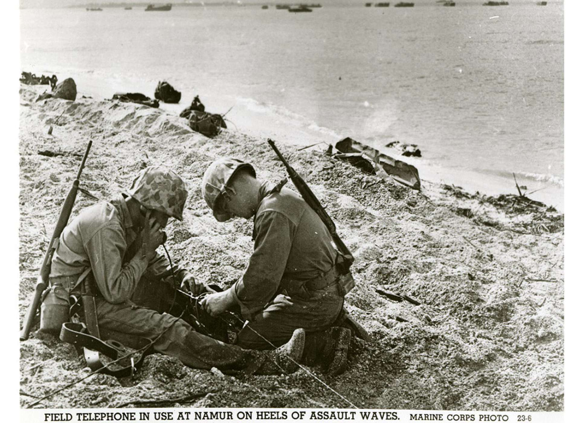 "Two United States Marines using a field telephone on a beach; debris is scattered throughout; landing craft are in the ocean in the background. Official caption on front: ""Field telephone in use at Namur on heels of assault waves. Marine Corps Photo 23-6."" Roi-Namur, Kwajalein Atoll, Marshall Islands. February 1944. Gift in memory of Sgt. Lyle E. Eberspecher, 2013.495.286"