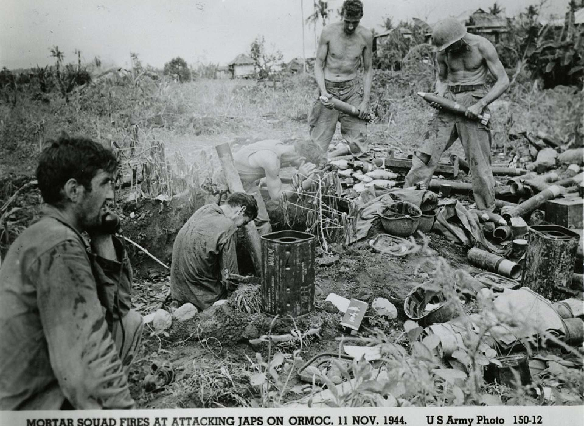 "Two United States Army soldiers holding mortar bombs next to two other soldiers who are firing the mortar; another soldier is talking into a field telephone. Official caption on front: ""Mortar squad fires at attacking Japs on Ormoc, 11 Nov. 1944. US Army Photo 150-12."" Ormoc, Leyte, Philippines. 11 November 1944. Gift in memory of Sgt. Lyle E. Eberspecher, 2013.495.930"