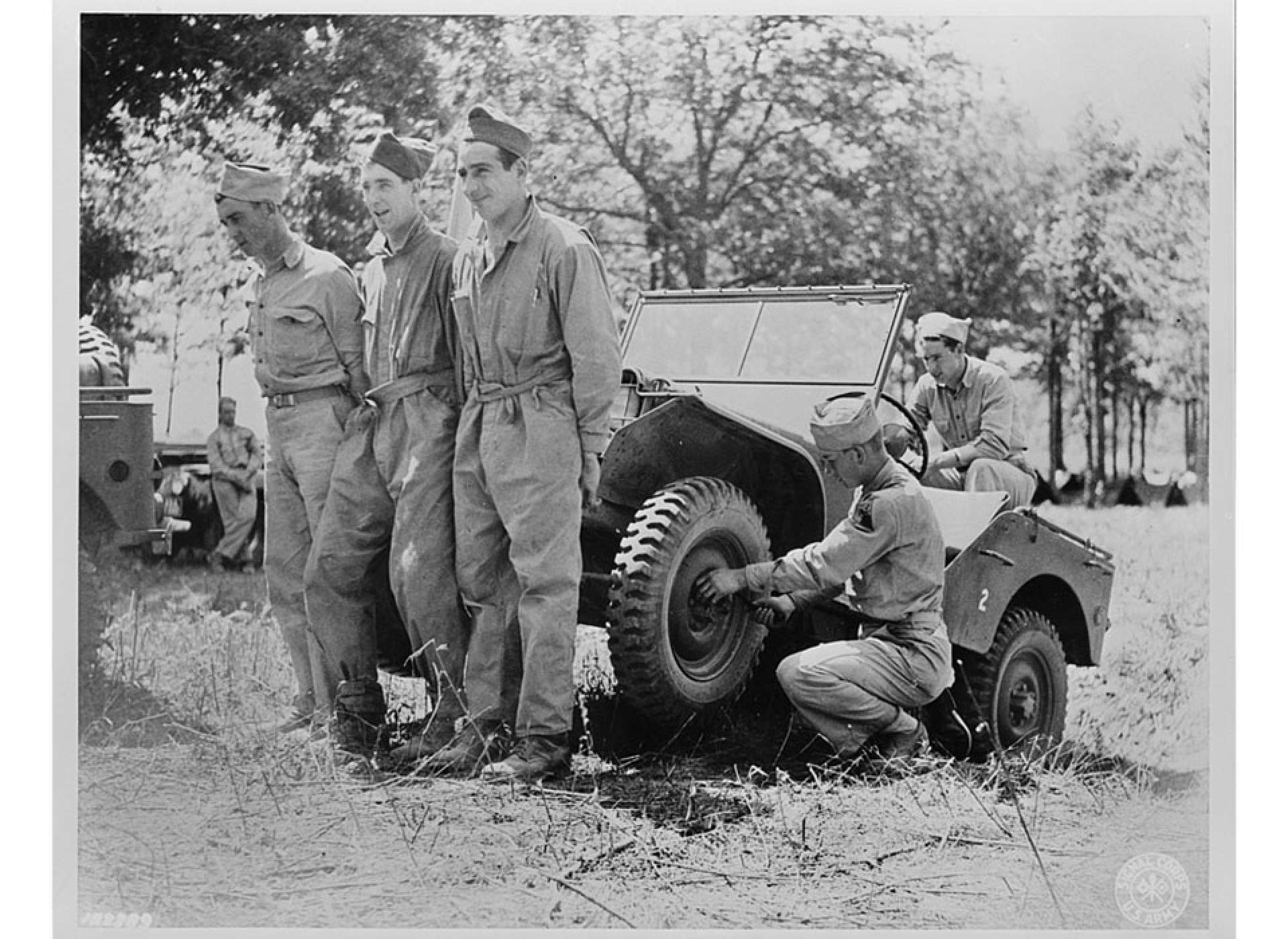 Soldiers of headquarters company of the Armored Corps lifting a jeep to repair it at their bivouac area during Second Army maneuvers, June 1941. Library of Congress